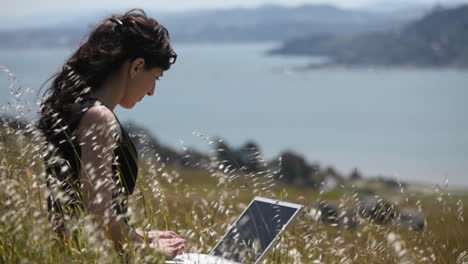 A-woman-sits-in-the-grass-and-uses-her-laptop