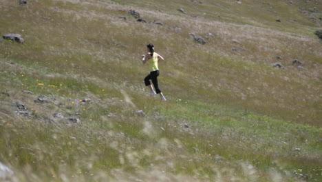 A-young-woman-runs-up-a-hillside