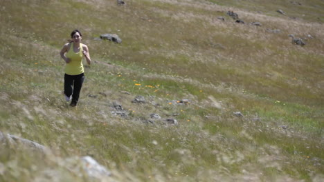 A-woman-jogs-up-the-rough-terrain-of-a-hill