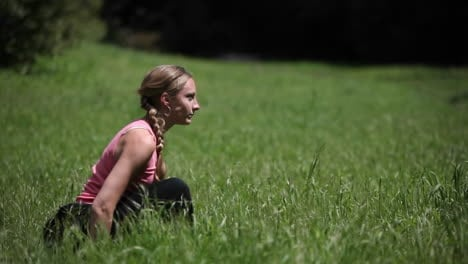 A-woman-does-yoga-poses-outside-in-the-grass