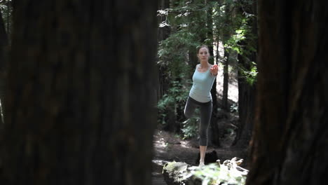 A-woman-stretches-in-the-midst-of-a-forested-area