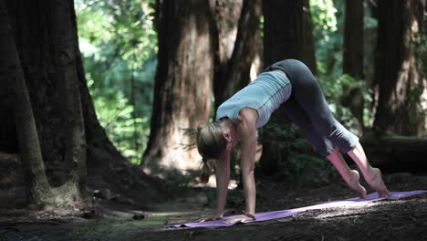 A-young-caucasian-woman-practicing-yoga-in-the-woods-along-a-river