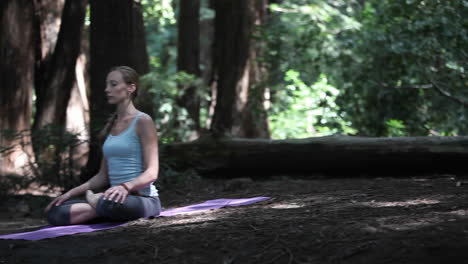 A-young-woman-practices-yoga-in-a-quiet-forest