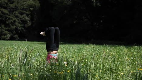 A-woman-doing-yoga-in-a-field-falls-over-from-her-head-stand