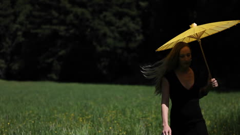 A-young-woman-walks-through-a-grassy-field-carrying-a-yellow-parasol