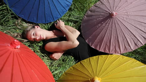 A-woman-lays-on-her-back-in-a-grassy-field-surrounded-my-different-colored-umbrellas