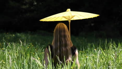A-woman-sits-in-the-grass-with-a-yellow-umbrella