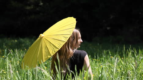 A-woman-sits-in-a-tall-grassy-field-with-an-umbrella