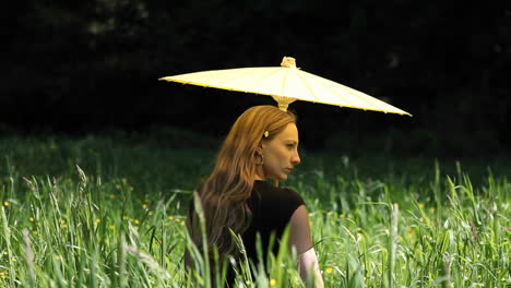 A-young-woman-with-an-umbrella-standing-in-tall-grass