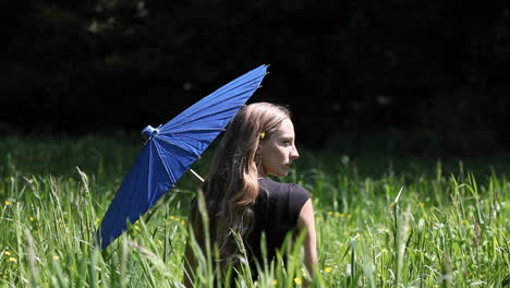 A-woman-sits-in-a-grassy-field-holding-a-blue-umbrella