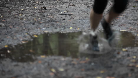 A-woman-jogs-over-a-puddle-reflecting-the-woods-of-the-area-where-she-is
