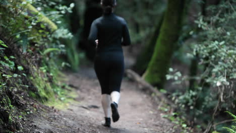 A-woman-jogs-on-a-path-in-a-wooded-area