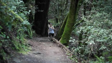 Women-enjoying-a-brisk-paced-jog-along-a-dirt-path-in-the-woods