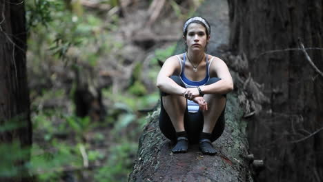 A-young-woman-sits-on-a-fallen-log-in-a-forest-puts-her-head-down-then-lifts-it-up