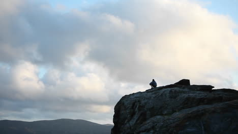 A-person-sits-at-the-top-of-a-rocky-mountain