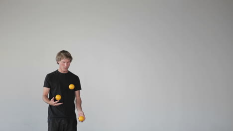 A-man-juggles-three-orange-balls-using-both-his-hands-and-his-legs
