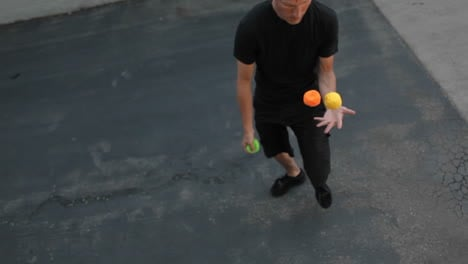 A-man-juggles-three-colored-balls-using-both-his-hands-and-his-feet-1