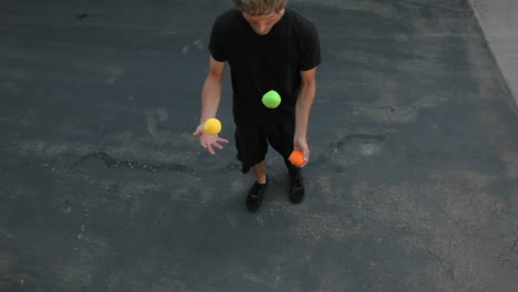 A-man-does-a-juggling-act-in-the-street-with-three-colored-balls