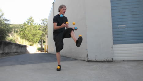 A-man-juggles-five-colored-balls-using-his-feet-as-well-as-his-hands