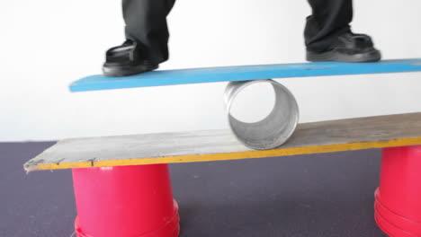 A-man-balances-on-a-board-and-a-tube