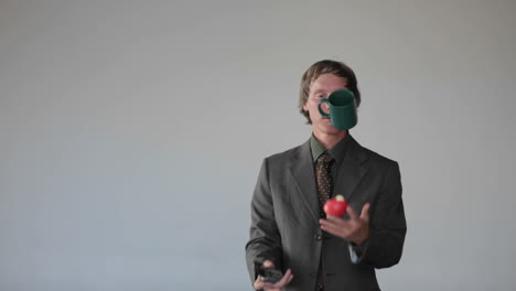 A-man-does-a-juggling-act-with-an-apple-a-cup-and-a-phone-answering-the-phone-and-catching-the-apple-in-the-cup