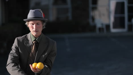 A-man-does-a-juggling-act-using-three-orange-balls