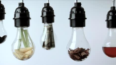 Bombillas-Que-Contienen-Materia-Vegetal-Dinero-Doblado-Y-Líquido-Rojo-Cuelgan-En-Una-Fila-Sobre-Un-Fondo-Blanco-