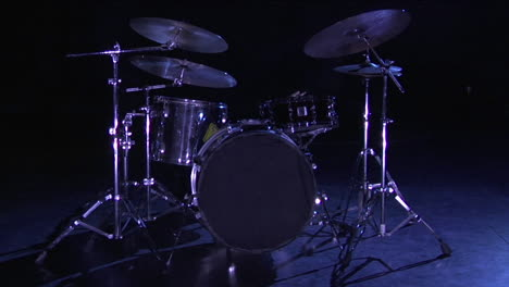A-drum-set-sits-on-a-dark-stage