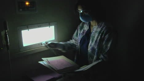 A-dental-hygienist-looks-at-xrays-in-a-darkened-room