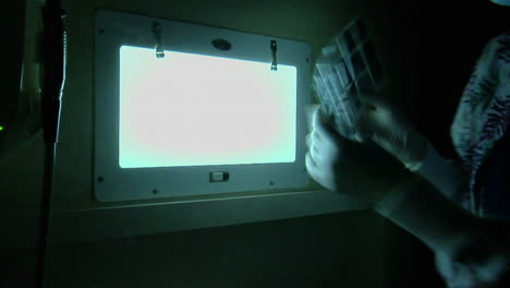 Un-Higienista-Dental-Mira-Radiografías-En-Una-Habitación-Oscura-2