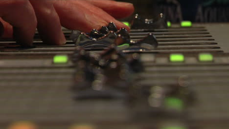 Fingers-push-sliders-on-a-sound-board