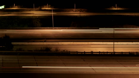 Vehicles-drive-on-a-freeway-at-night-in-fast-motion