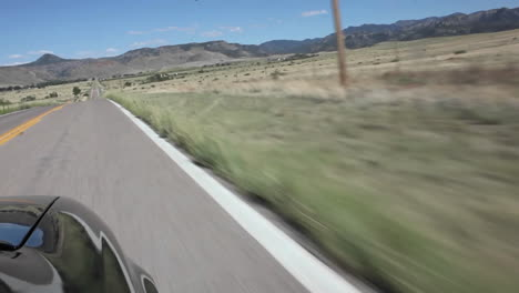 A-car-driving-down-a-country-road-POV