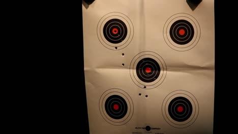 Un-Hombre-Mira-A-La-Cámara-Y-Luego-Dispara-Una-Pistola-A-Un-Objetivo-En-Un-Campo-De-Tiro-Interior-1
