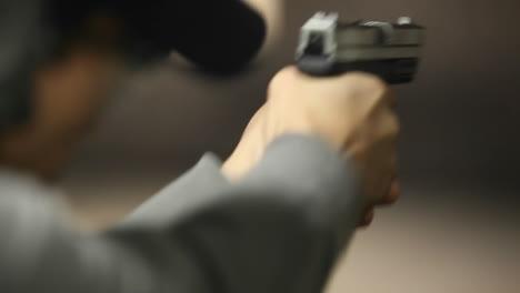 Un-Hombre-Dispara-Una-Pistola-De-Mano-A-Un-Objetivo-En-Un-Campo-De-Tiro-Interior