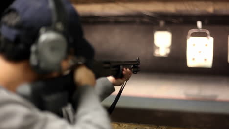 A-man-fires-a-rifle-at-a-target-at-an-indoor-shooting-range