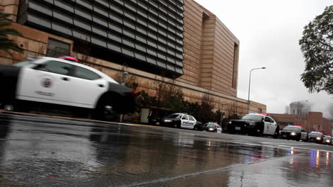 A-line-of-police-vehicles-pass-along-a-street-on-a-rainy-day