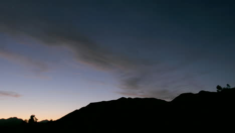 Clouds-move-over-a-silhouetted-mountain-during-golden-hour