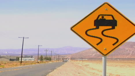 Cars-pass-by-a-slippery-when-wet-road-sign-along-a-lonely-desert-highway
