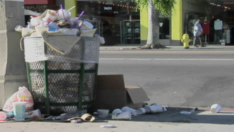 Trash-spills-out-of-an-overfilled-trash-can-on-a-city-street