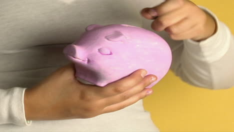 A-woman-places-coins-into-a-piggy-bank