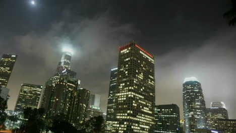Heavy-traffic-drives-on-a-busy-freeway-in-a-city-at-night-in-downtown-Los-Angeles-with-fog-rolling-in-1