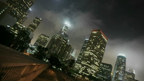 Heavy-traffic-drives-on-busy-streets-at-night-in-downtown-Los-Angeles-with-fog-rolling-in