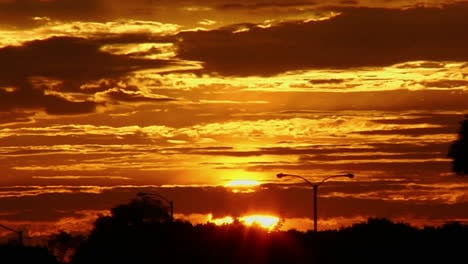 The-sun-glows-behind-clouds-in-a-red-and-orange-sky