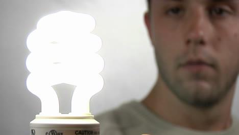 A-young-man-gazes-at-a-compact-fluorescent-light-bulb-as-it-lights