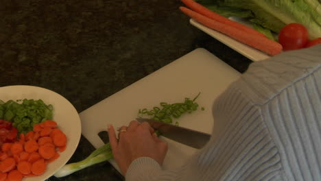 A-woman-chops-green-onions-on-a-cutting-board