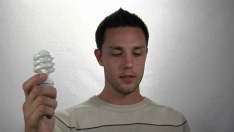 A-man-holds-a-compact-fluorescent-light-bulb-in-one-hand-and-money-in-the-other