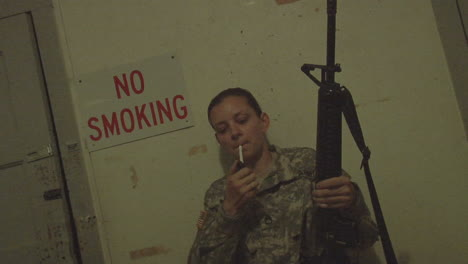 A-solider-lights-a-cigarette-in-front-of-a-No-Smoking-sign
