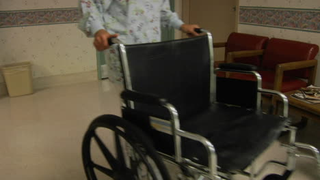 A-nurse-wheels-an-empty-wheelchair-through-a-hospital-lobby