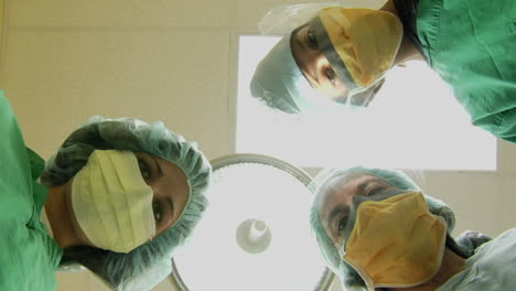 Surgeons-look-down-on-a-patient-and-use-instruments-in-this-POV-shot-1